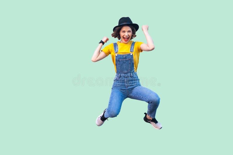 Portret van gillend gelukkig verrast jong meisje in blauwe denimoverall, geel overhemd en het zwarte hoed springen, die eruit zie royalty-vrije stock afbeeldingen