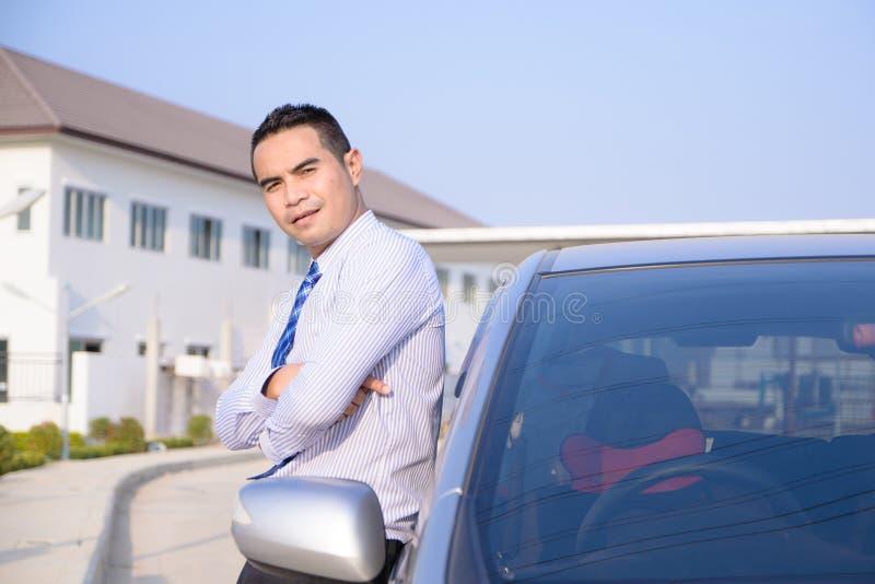Portret van glimlach de Aziatische bedrijfsmens die zich met auto en huis bevinden royalty-vrije stock afbeeldingen