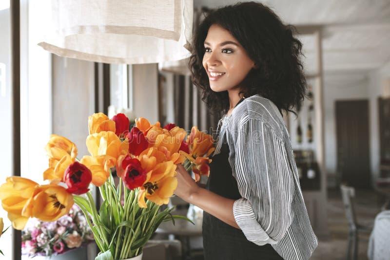 Portret van glimlachend Afrikaans Amerikaans meisje met donker krullend zich met bloemen bevinden en haar die opzij eruit zien stock fotografie
