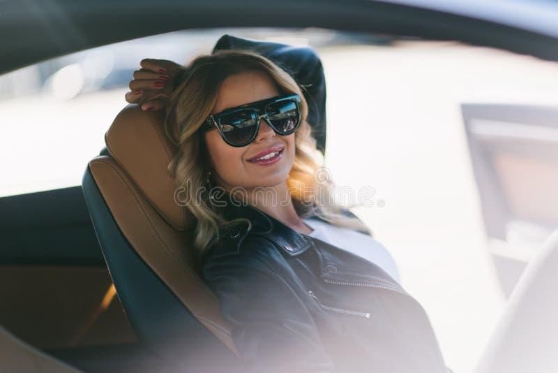 Portret van glimlachend blonde met lang haar achter wiel in auto royalty-vrije stock afbeeldingen
