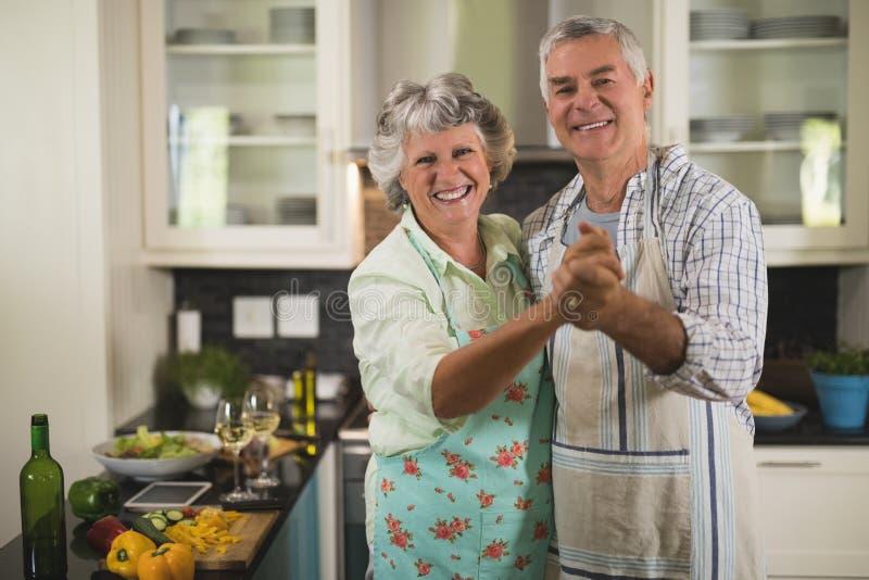 Portret van glimlachend hoger paar die in keuken dansen stock afbeeldingen