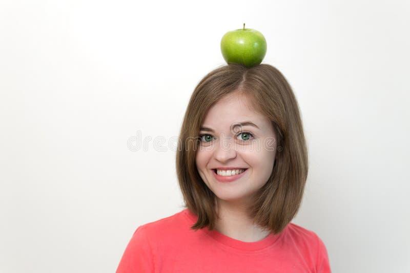 Portret van glimlachend Kaukasisch vrouwenmeisje met groene appel op haar hoofd Gezonde levensstijl, fruit vegetarisch dieet stock foto's