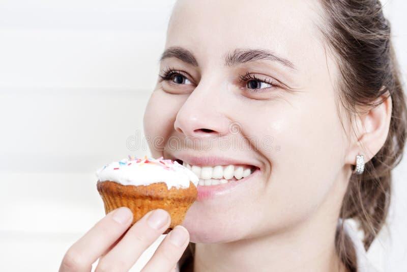 Portret van glimlachend meisje die muffin eten cupcake Mooie jonge aantrekkelijke Kaukasische meisjesgezicht het bijten muffin royalty-vrije stock afbeeldingen