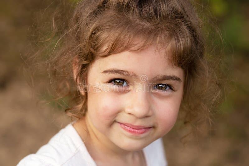 Portret van glimlachend mooi meisje in het zomerpark Cute child die naar de camera kijkt royalty-vrije stock afbeeldingen