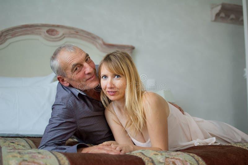 Portret van Glimlachend Paar met Leeftijdsverschil Mooie Jonge Vrouw met Haar Hogere Minnaar die op het Bed liggen Mens royalty-vrije stock afbeelding