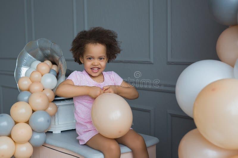 Portret van glimlachend zwart meisje met een dichtbije ballon stock afbeelding