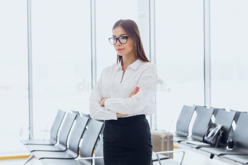 Portret van glimlachende aantrekkelijke bedrijfsvrouw in luchthavenzaal De ruimte van het exemplaar stock foto
