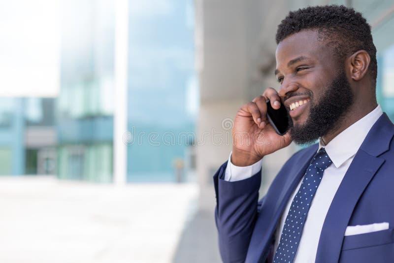 Portret van glimlachende Afrikaanse Amerikaanse zakenman in kostuum die telefonisch met exemplaarruimte spreken royalty-vrije stock fotografie