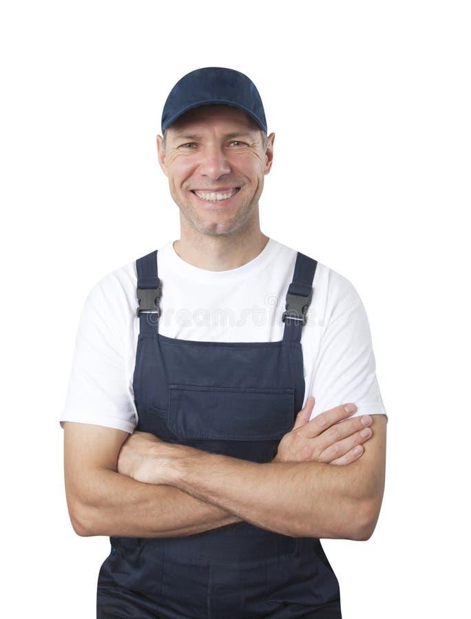 Portret van glimlachende arbeider in blauwe eenvormig die op witte bac wordt geïsoleerd stock afbeeldingen
