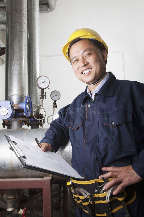 Portret van glimlachende arbeider met een klembord die het materiaal van de oliepijpleiding in een gasinstallatie controleren, Pek royalty-vrije stock foto's