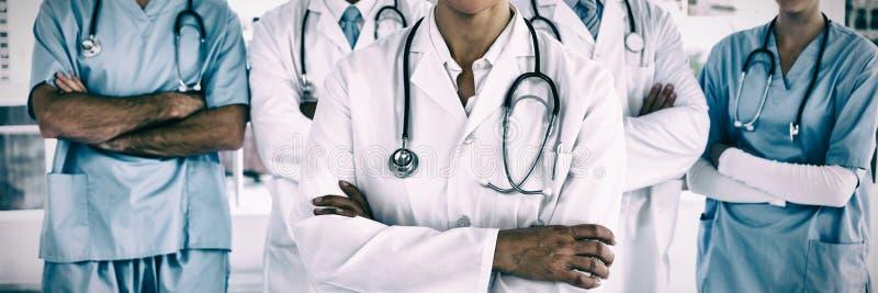 Portret van glimlachende artsen die zich met gekruiste wapens bevinden stock foto