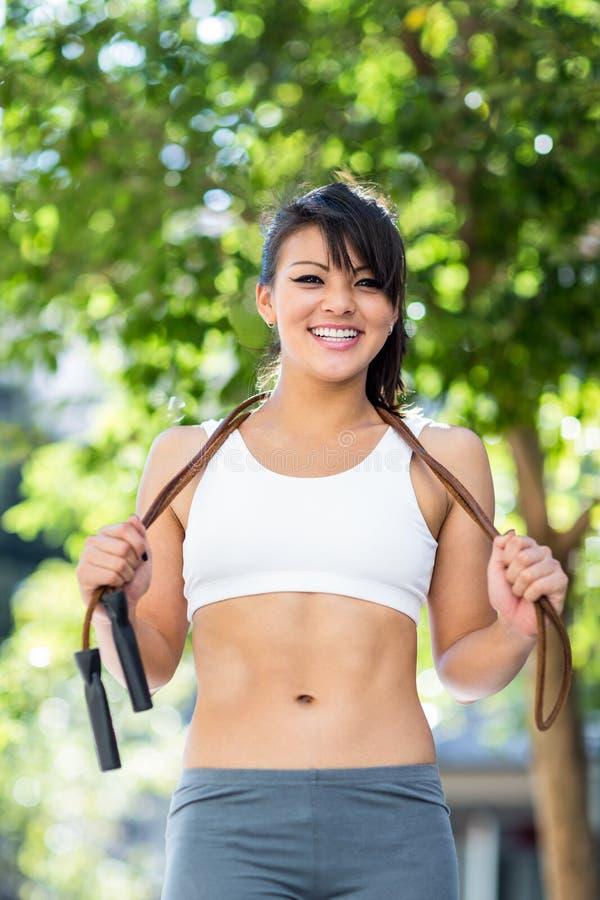 Portret van glimlachende atletische vrouw die met touwtjespringen camera bekijken stock foto