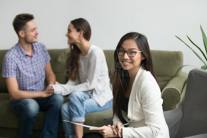 Portret van glimlachende Aziatische adviseur met gelukkig paar bij backgro stock fotografie