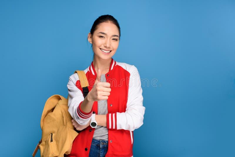 portret van glimlachende Aziatische student die duim tonen stock afbeelding