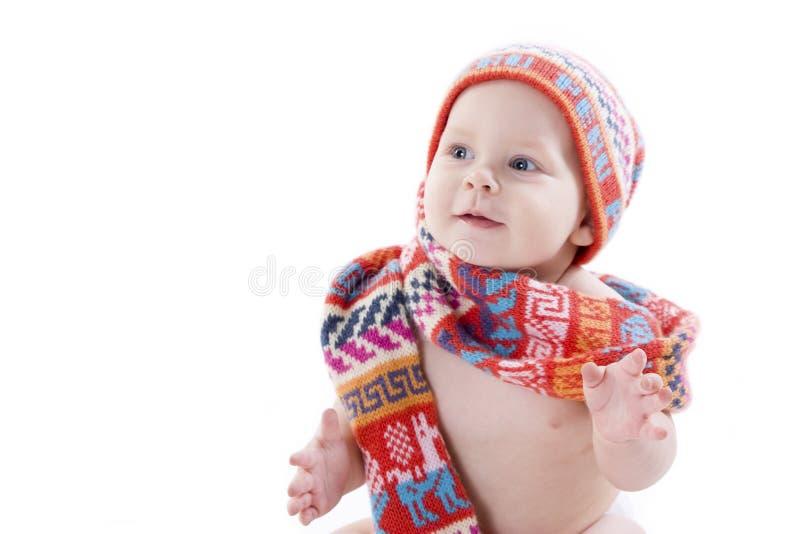 Portret van glimlachende baby in gebreide hoed en sjaal stock foto