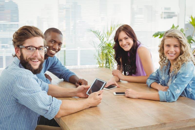 Portret van glimlachende bedrijfsberoeps die technologie gebruiken bij bureau stock afbeelding