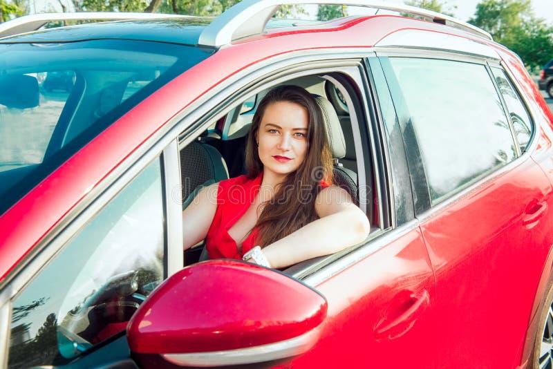 Portret van glimlachende bedrijfsdame, Kaukasische jonge vrouwenbestuurder in rode camera bekijken en kleren die terwijl erachter royalty-vrije stock afbeelding