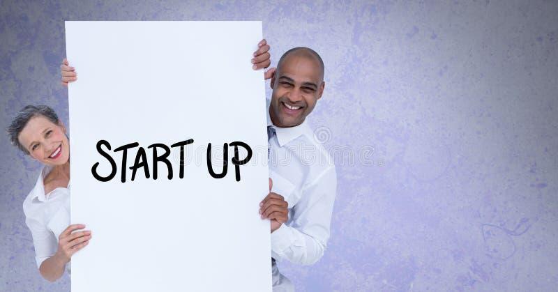 Portret van glimlachende bedrijfsmensen die aanplakbord met starttekst houden tegen grijze achtergrond stock afbeeldingen