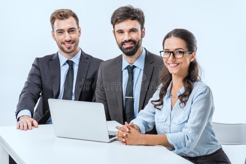 portret van glimlachende bedrijfsmensen die camera bekijken terwijl het zitten op het werk stock foto's