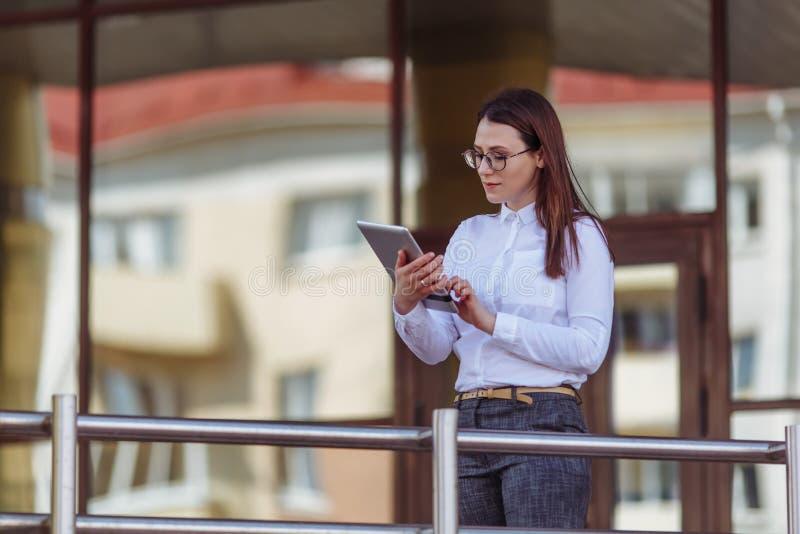 Portret van glimlachende bedrijfsvrouw die tabletpc voor de bureaubouw met behulp van stock afbeelding
