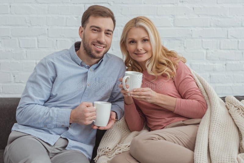 portret van glimlachende familie met koppen van koffie het rusten stock fotografie