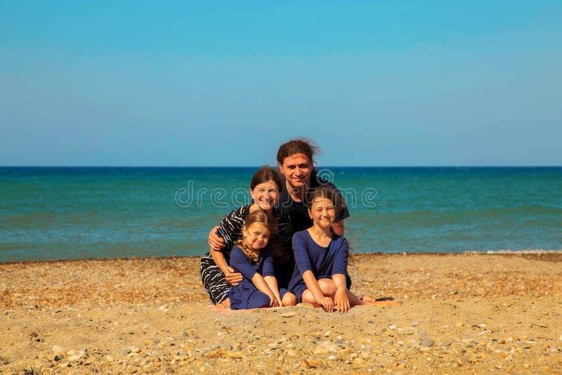 Portret van glimlachende familie op het strand tegen het overzees stock foto