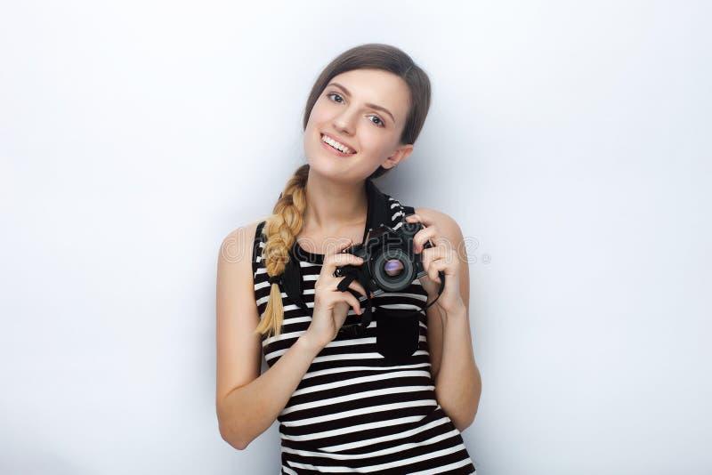 Portret van glimlachende gelukkige jonge mooie vrouw in het gestreepte overhemd stellen met zwarte fotocamera tegen studioachterg royalty-vrije stock afbeeldingen