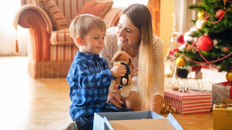 Portret van glimlachende gelukkige moeder die haar bekijken weinig Kerstmisgift van de zoonsholding stock afbeeldingen