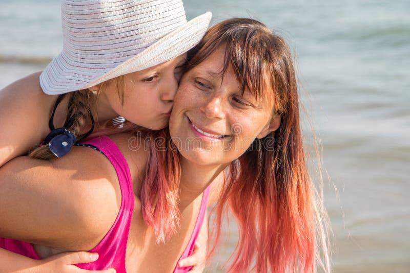 Portret van glimlachende gelukkige moeder en weinig dochter die samen op zonnig strand lachen royalty-vrije stock foto
