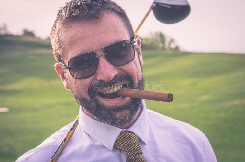 Portret van glimlachende golfspeler met sigaar met bestuurder stock fotografie