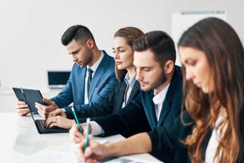 Portret van glimlachende groep bedrijfsmensen die op een rij samen bij lijst in een modern bureau zitten stock foto