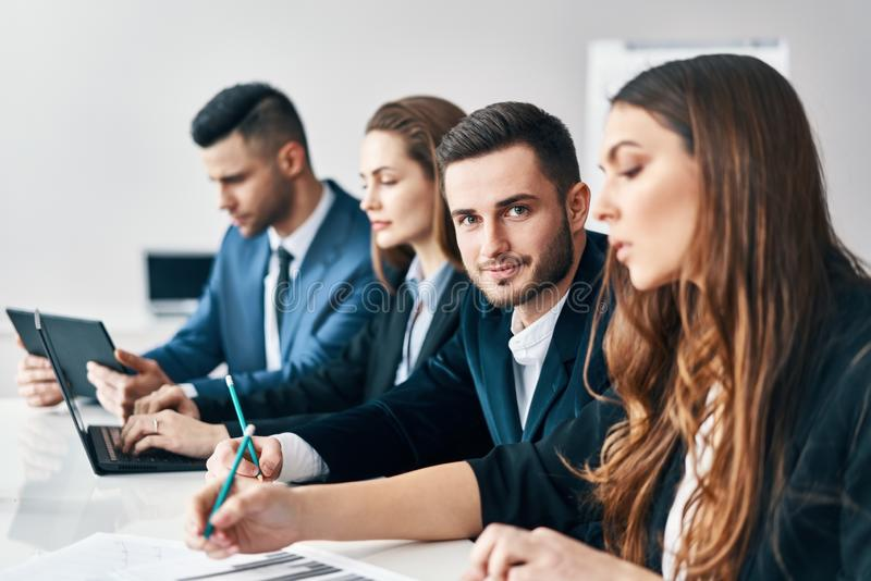 Portret van glimlachende groep bedrijfsmensen die op een rij samen bij lijst in een modern bureau zitten stock foto's