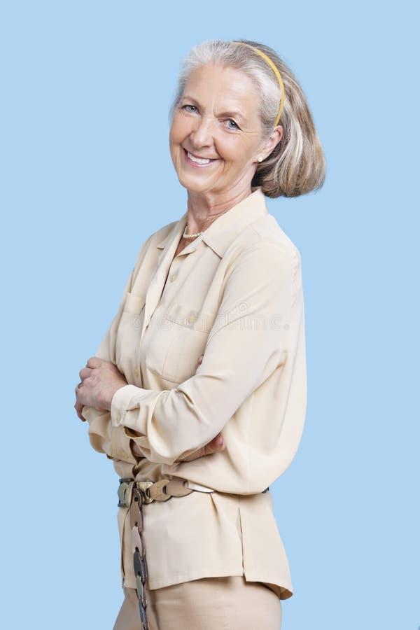 Portret van glimlachende hogere die vrouw in toevallig met wapens tegen blauwe achtergrond worden gekruist royalty-vrije stock afbeeldingen