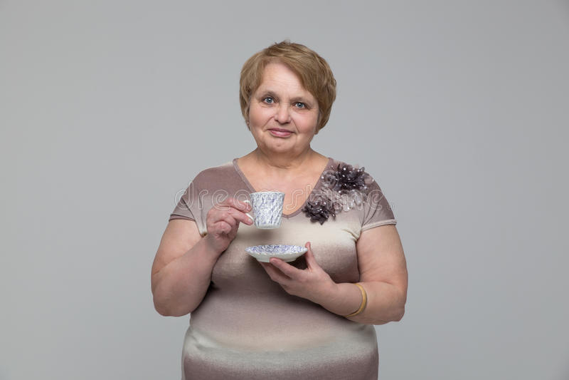 Portret van glimlachende hogere vrouw met kop thee stock foto