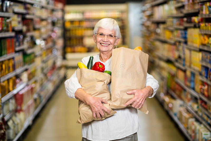 Portret van glimlachende hogere vrouw met kruidenierswinkelzakken royalty-vrije stock foto's