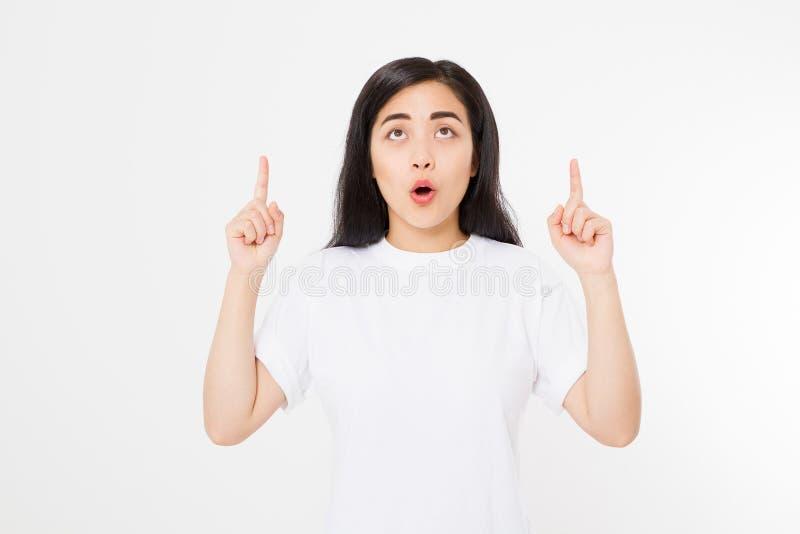 Portret van glimlachende jonge Aziatische vrouw die de zomert-shirt dragen die op exemplaarruimte door vinger richten die op witt stock afbeelding