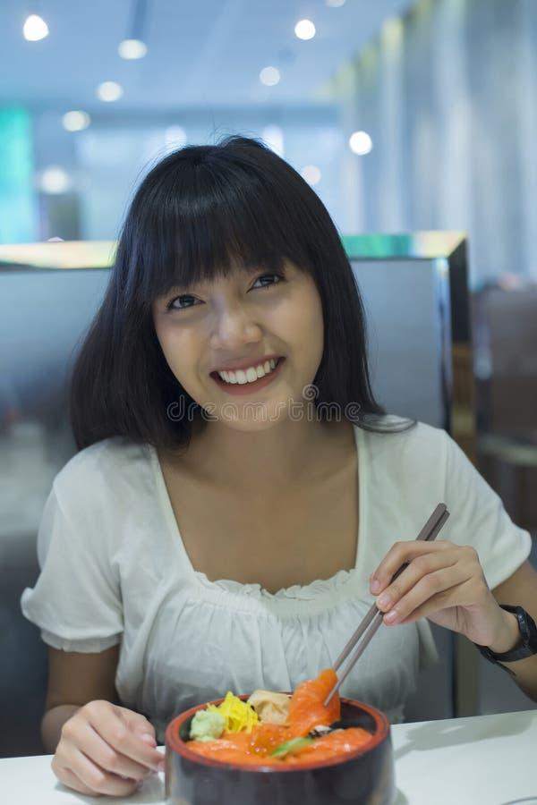 Portret van glimlachende jonge Aziatische vrouw die Japans voedsel eten royalty-vrije stock foto's