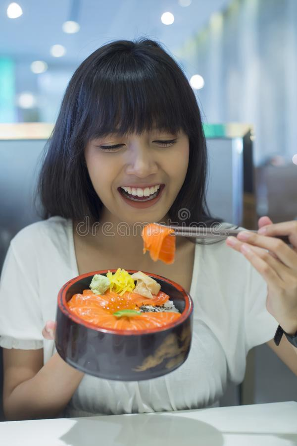 Portret van glimlachende jonge Aziatische vrouw die Japans voedsel eten stock fotografie