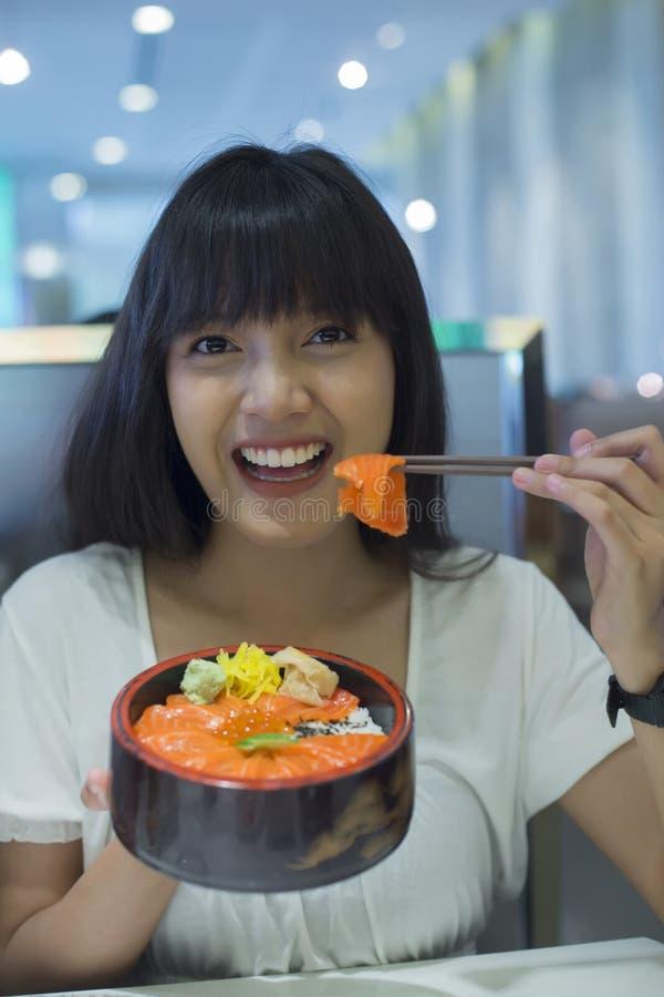 Portret van glimlachende jonge Aziatische vrouw die Japans voedsel eten stock foto's
