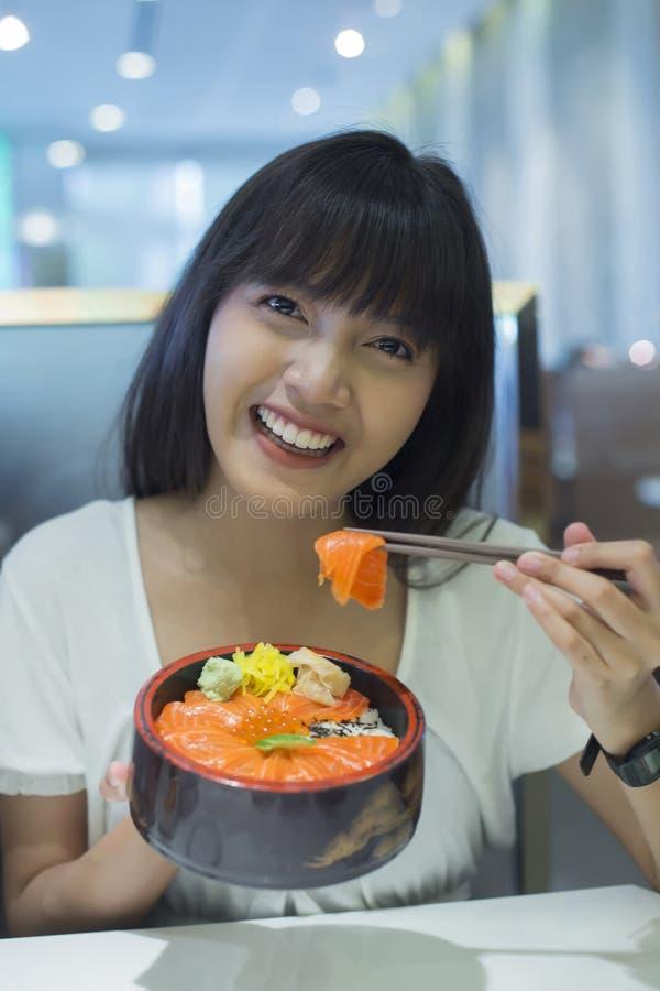Portret van glimlachende jonge Aziatische vrouw die Japans voedsel eten royalty-vrije stock foto
