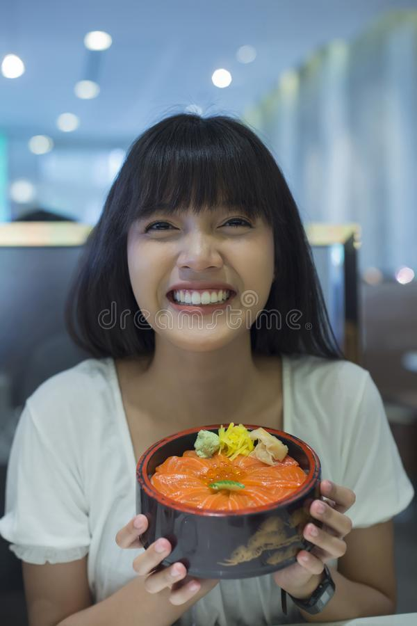 Portret van glimlachende jonge Aziatische vrouw die Japans voedsel houden royalty-vrije stock foto's