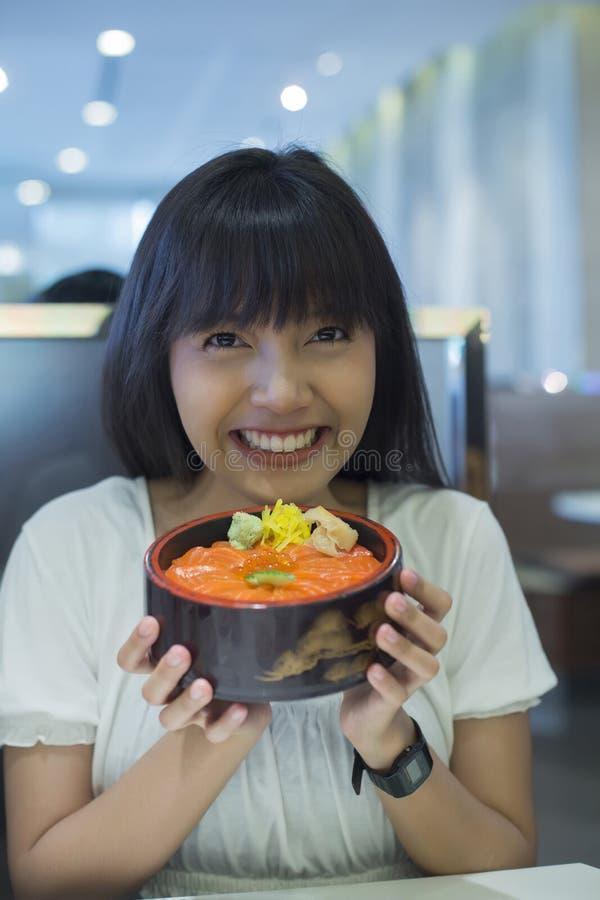 Portret van glimlachende jonge Aziatische vrouw die Japanse voedselschotel houden royalty-vrije stock foto