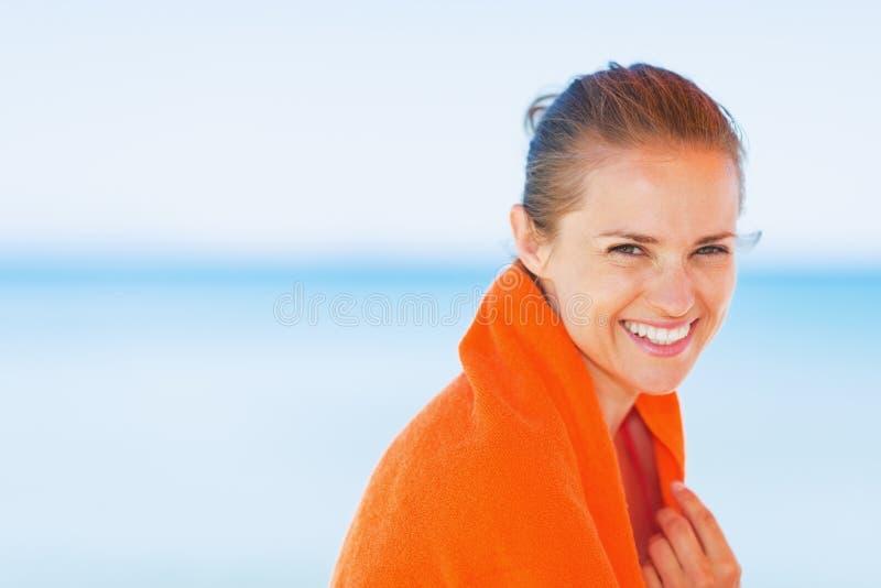 Portret van glimlachende jonge die vrouw in handdoek op strand wordt verpakt stock fotografie