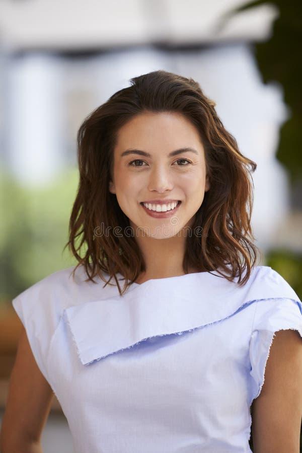 Portret van glimlachende jonge gemengde verticaal rasonderneemster, stock foto