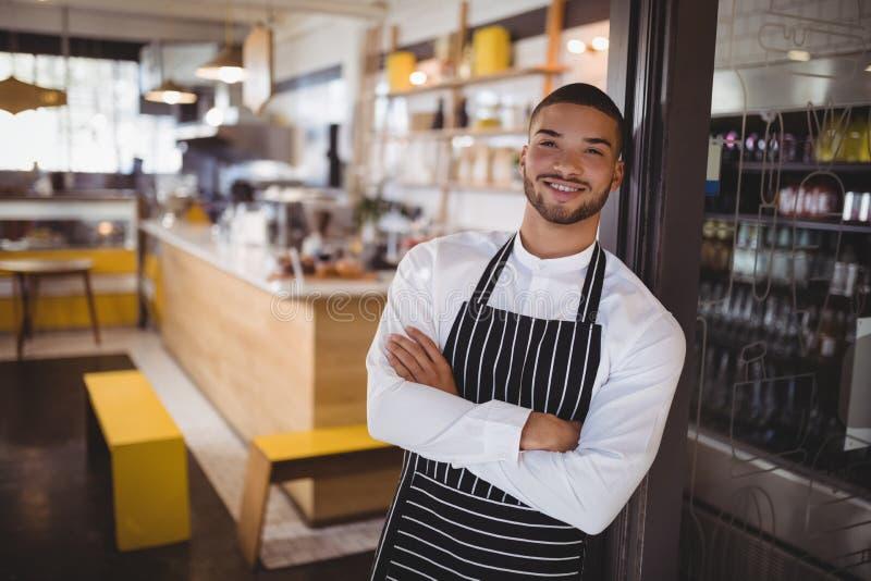 Portret van glimlachende jonge knappe kelner met gekruiste wapens het leunen op kabinet stock foto