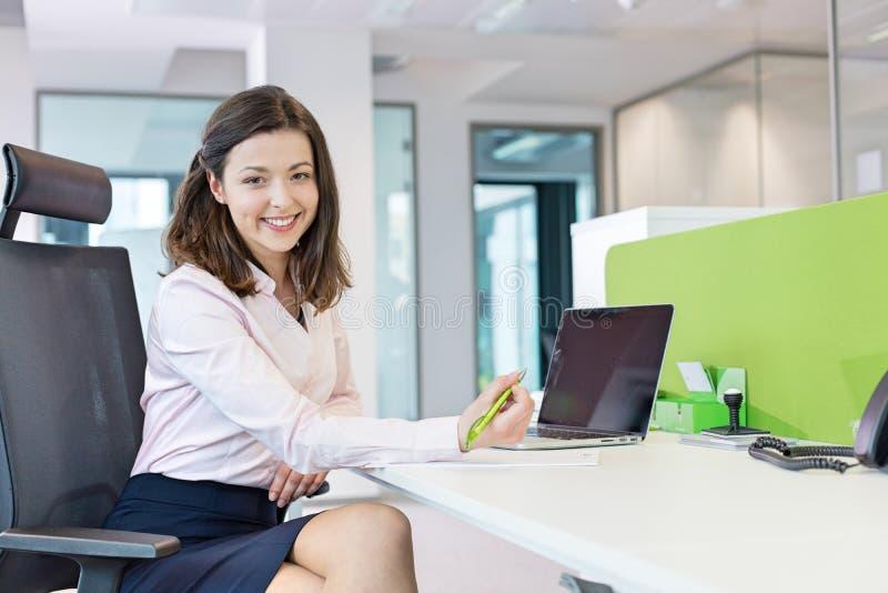 Portret van glimlachende jonge onderneemster die op document in bureau schrijven royalty-vrije stock foto