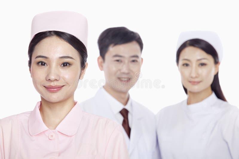 Portret van glimlachende jonge verpleegster, arts en verpleegster op de achtergrond, studioschot royalty-vrije stock fotografie