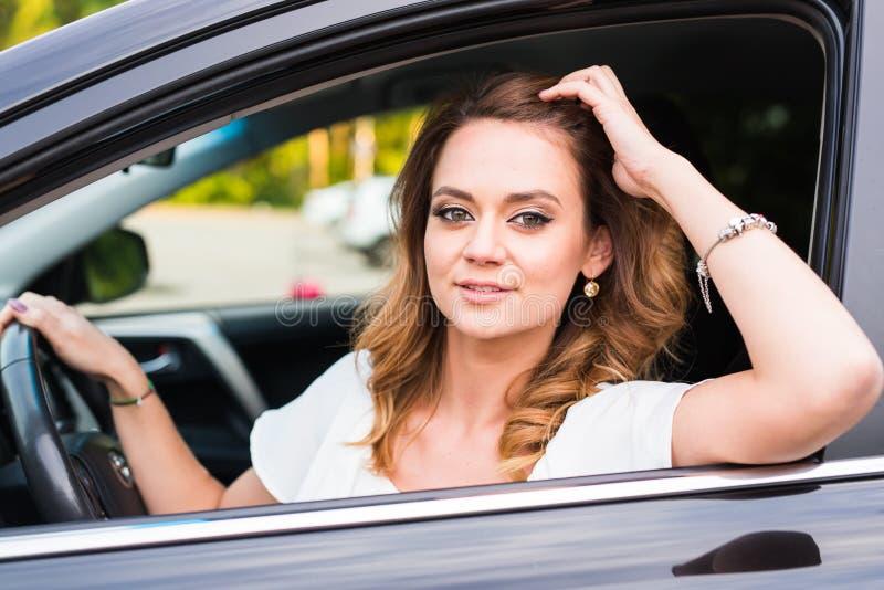 Portret van glimlachende jonge vrouw die een auto drijven royalty-vrije stock afbeelding