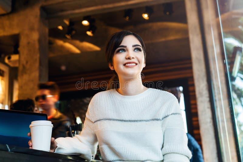 Portret van glimlachende jonge vrouw die met document kop van koffie in haar handen, bij lijst in koffie zitten, die uit venster  royalty-vrije stock afbeeldingen