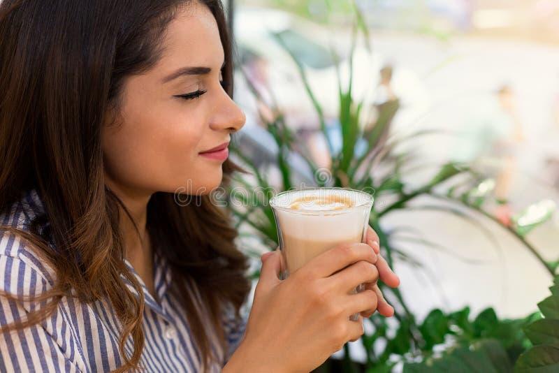 Portret van glimlachende jonge vrouw die ochtend van koffie in koffie genieten royalty-vrije stock fotografie